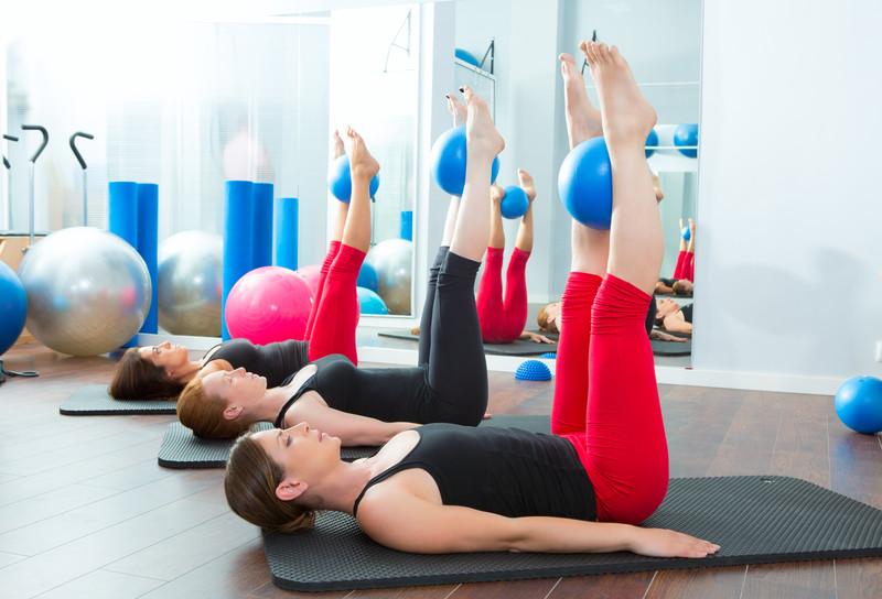 women on mats in studio doing Pilates