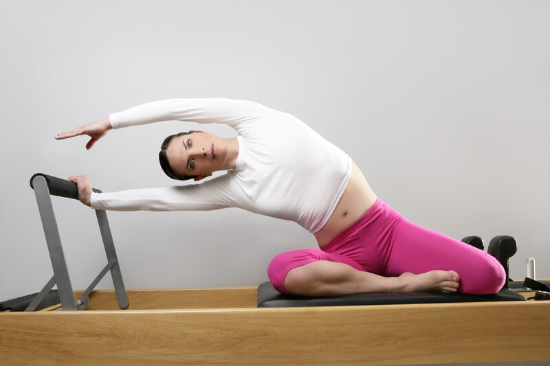 woman on mat stretching with bar in exercise clothes